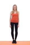 Lächelnde Frau in den Sportkleidungstrainingsbeinen und -händen auf einer Matte stockfotografie