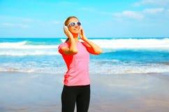 Lächelnde Frau der Eignung hört Musik in den drahtlosen Kopfhörern auf dem Strand Stockbilder