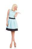 Lächelnde Frau in der hellblauen Farbe kleiden das Darstellen des Produktes Stockfoto