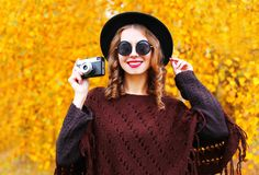 Lächelnde Frau der Herbstmode mit Retro- Kamera im schwarzen runden Hut Stockbild