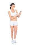 Lächelnde Frau in der Sportkleidung unter Verwendung des Telefons Lizenzfreie Stockfotografie