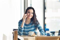 Lächelnde Frau an der Stange, die einen Telefonanruf hat Stockfoto