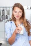 Lächelnde Frau in der Trinkmilch der Küche Stockfotos