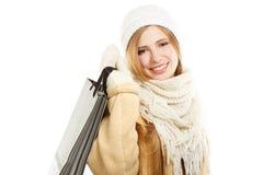 Lächelnde Frau in der warmen Kleidung mit Tasche Stockfoto
