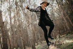 Lächelnde Frau in der zufälligen Kleidung gehend auf einen gefallenen Baumstamm im Wald Stockbild