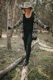 Lächelnde Frau in der zufälligen Kleidung gehend auf einen gefallenen Baumstamm in der Natur Stockfoto