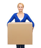 Lächelnde Frau in der zufälligen Kleidung mit Paketkasten Stockfoto