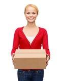 Lächelnde Frau in der zufälligen Kleidung mit Paketkasten Stockbild