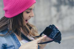 Lächelnde Frau in der zufälligen Kleidung und rosa im Hut, die Kamera hält und gutem Schuss machte sie zeigt, während des Straßen stockfoto