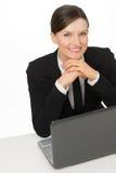 Lächelnde Frau des Geschäfts mit dem Laptop, der mit offenen Augen sitzt Stockfoto