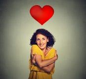 Lächelnde Frau des Porträts, die das Umarmen mit rotem Herzen über Kopf hält Lizenzfreie Stockfotos