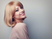 Lächelnde Frau des schönen Zahnes mit dem kurzen blonden Haar, das happ schaut Stockfoto