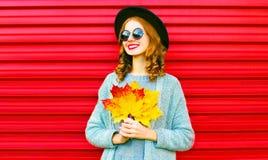 Lächelnde Frau des stilvollen glücklichen Porträts mit gelben Ahornblättern Lizenzfreie Stockfotografie