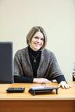 Lächelnde Frau am desc mit Computermonitor Stockbilder