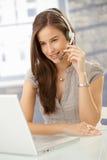 Lächelnde Frau, die über Kopfhörer spricht Lizenzfreie Stockfotografie
