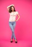 Lächelnde Frau, die über rosa Hintergrund aufwirft Stockfoto