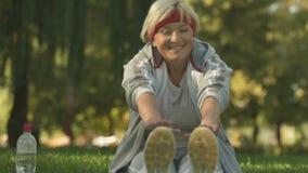 Lächelnde Frau, die Übung im Park, Morgengymnastik draußen ausdehnend tut stock video