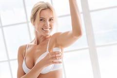 Lächelnde Frau, die Antitranspirationsmittel nach Badezimmer verwendet Stockfoto