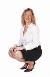 Lächelnde Frau, die auf Boden sich duckt Lizenzfreie Stockfotos