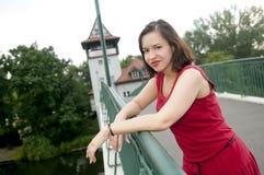 Lächelnde Frau, die auf Brücke steht Stockfotografie