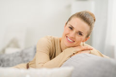 Lächelnde Frau, die auf Couch im Wohnzimmer sitzt Stockfoto