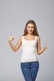 Lächelnde Frau, die auf das Zujubeln glücklich, auf grauem backgr zeigt stockbild