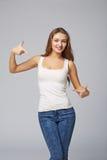 Lächelnde Frau, die auf das Zujubeln glücklich, auf grauem backgr zeigt lizenzfreies stockbild
