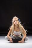 Lächelnde Frau, die auf dem Boden in den Kopfhörern sitzt Stockbild
