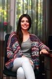 Lächelnde Frau, die auf dem Chai sitzt Lizenzfreie Stockfotos