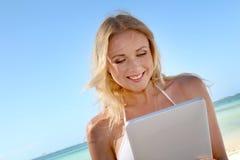 Lächelnde Frau, die auf dem Strand websurfing ist Lizenzfreie Stockfotografie