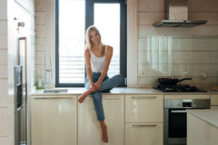 Lächelnde Frau, die auf dem Tisch in der Küche sitzt Lizenzfreie Stockfotos