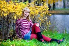 Lächelnde Frau, die auf der Flussquerneigung sitzt Lizenzfreies Stockbild