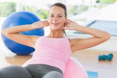 Lächelnde Frau, die auf Eignungsball an der Turnhalle trainiert Lizenzfreies Stockbild