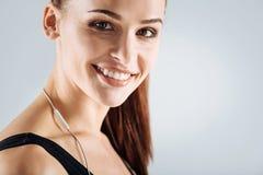 Lächelnde Frau, die auf einem grauen Hintergrund nach der Ausbildung aufwirft lizenzfreie stockfotos