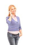Lächelnde Frau, die auf einem Handy spricht Stockbild