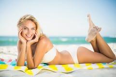 Lächelnde Frau, die auf einem Tuch am Strand liegt Lizenzfreie Stockbilder