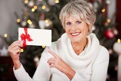 Lächelnde Frau, die auf einen Weihnachtsbeleg zeigt Stockfotografie