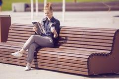Lächelnde Frau, die auf einer Bank mit Kaffee und dem Ablesen von magazin sitzt Stockfoto