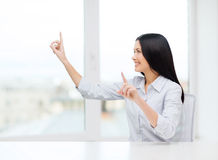 Lächelnde Frau, die auf etwas eingebildet zeigt Stockbilder
