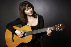 Lächelnde Frau, die auf Gitarre spielt. Stockfotos