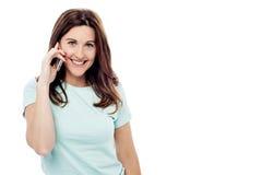 Lächelnde Frau, die auf ihrem Mobile spricht Stockfoto
