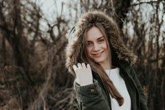 Lächelnde Frau, die auf Kamera in der Jacke mit Pelzhaube aufwirft Lizenzfreie Stockfotografie