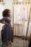 Lächelnde Frau, die auf Kleid im Umkleideraum, vertikal versucht stockfoto