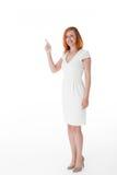 Lächelnde Frau, die auf leeres copyspace zeigt Stockfotos