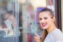 Lächelnde Frau, die auf Schaukasten zeigt Stockfotografie