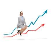 Lächelnde Frau, die auf wachsendem Diagramm sitzt stockfotografie