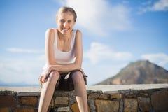 Lächelnde Frau, die auf Wand sitzt Stockfotografie