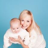 Lächelnde Frau, die Baby über Blau hält Stockbilder