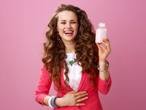 Lächelnde Frau, die Bauernhof organischen Jogurt zeigt und Bauch reibt Stockbilder