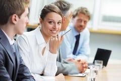 Lächelnde Frau, die bei einem Geschäftstreffen mit Kollegen sitzt Stockfotografie